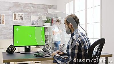 Un homme travaille sur un écran de PC fictif à la table dans un salon lumineux et lumineux banque de vidéos
