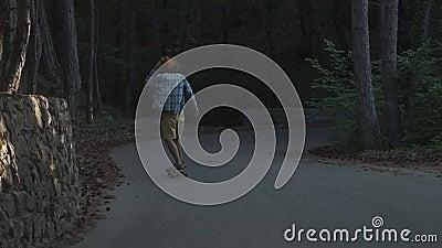 Un individuo joven aprende montar un longboard Está situado en el bosque vestido en una camisa de tela escocesa y un sombrero de  metrajes