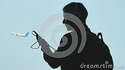 Un individuo joven da vuelta en música en un smartphone y pone los auriculares contra la perspectiva de un lanzamiento del avión metrajes