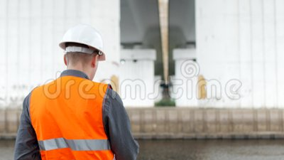 Un inspecteur d'homme examine l'état des colonnes du pont à travers la rivière et marque les points faibles banque de vidéos