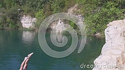 Un jeune homme aux oreilles s'écrase au large de Cliff dans l'eau bleue du lac. L'été en plein air Lifestyle clips vidéos
