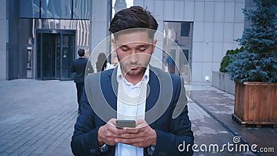 Un jeune homme d'affaires utilise un téléphone intelligent pour se promener dans la rue Big City Business District Street Habillé banque de vidéos