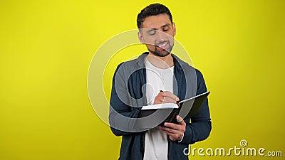 Un jeune homme en chemise bleue et T-shirt blanc écrit des tâches, des buts, des rêves, des idées dans un cahier avec un stylo no clips vidéos