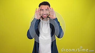 Un jeune homme en chemise bleue et T-shirt blanc ouvre son visage avec ses mains, sourit et regarde la caméra clips vidéos