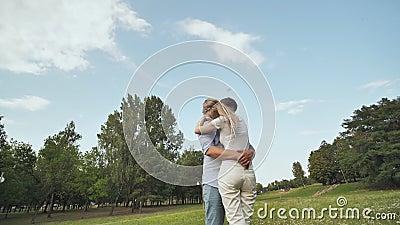 Un jeune homme et une femme se tiennent debout dans les parcs, se serrant les coudes. Vidéo en mouvement et rotation banque de vidéos