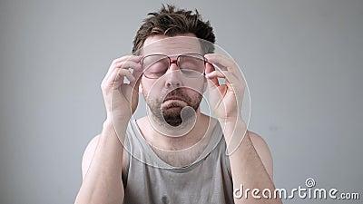 Un jeune homme regardant à travers d'immenses lunettes en état de choc avec une expression de surprise banque de vidéos