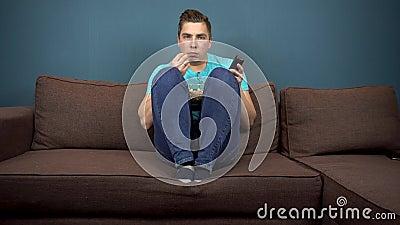 Un jeune homme regarde la télévision et mange du pop-corn Le type regarde la télé attentivement Un moment passionnant dans l'intr clips vidéos