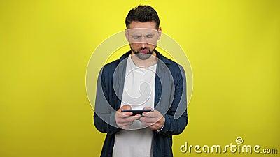 Un jeune homme vêtu d'une chemise bleue et d'un T-shirt blanc joue à un jeu sur un smartphone et perd, est contrarié clips vidéos