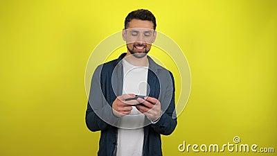 Un jeune homme vêtu d'une chemise bleue et d'un T-shirt blanc joue avec enthousiasme sur un smartphone banque de vidéos