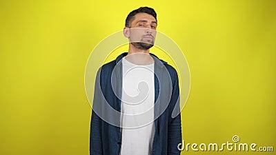 Un jeune homme vêtu d'une chemise bleue et d'un T-shirt blanc regarde autour de lui pour trouver du texte banque de vidéos