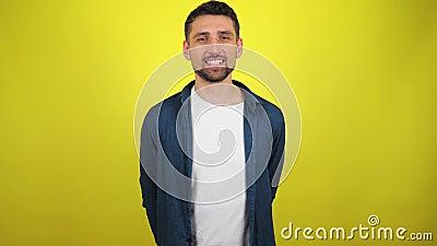 Un jeune homme vêtu d'une chemise bleue et d'un T-shirt blanc regarde la caméra, les flirts et les yeux des treuils banque de vidéos