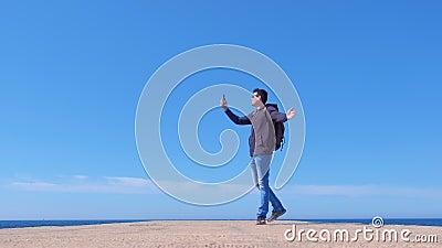 Un jeune homme voyageur blogueur parlant de chat vidéo marchant sur la jetée de la mer banque de vidéos