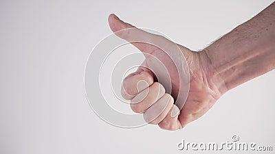 Un joven se junta los dedos y muestra una señal similar en su mano sobre un fondo blanco Lengua de señas internacional almacen de video
