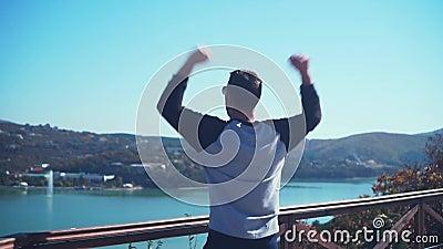 Un joven se levanta, mirando desde la baraja de observación y rebotando, levantando las manos con asombro de felicidad almacen de video