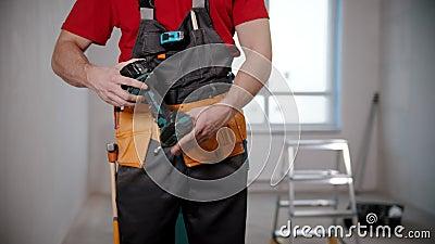 Un joven trabajador saca un instrumento grande de su cinturón de herramientas almacen de video