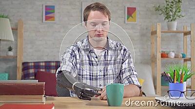 Un joven triste tiene dificultades para usar un brazo prostético biónico metrajes