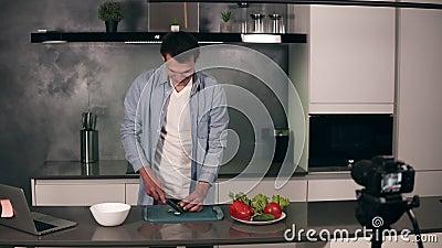 Un joven vestido con ropa informal dirige un blog culinario y graba un video en una cocina gris Grabación de video del blog - almacen de metraje de vídeo