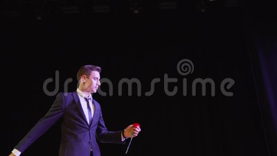 Un mago muestra un truco con una flor pintada El mago muestra el foco con la aparición de las flores metrajes