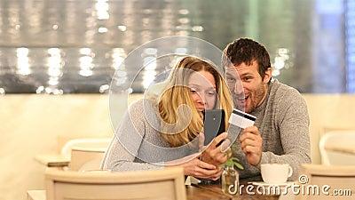 Un matrimonio emocionado encuentra ofertas de compra en línea en un bar metrajes