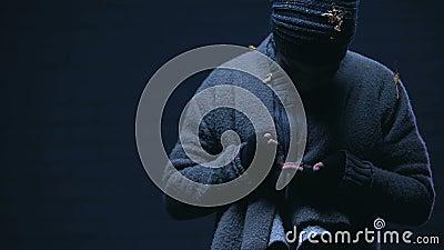 Un mendiant sale tenant et comptant soigneusement les pièces de monnaie, de la charité pour les pauvres banque de vidéos