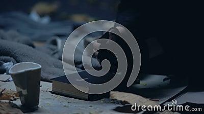 Un mendiant sans abri assis par terre avec de la bible et priant pour de l'aide, croyance forte banque de vidéos