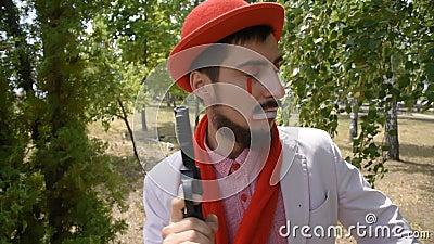 Un mimo pazzo sta cercando un criminale Il clown cerca le tracce dell'assassino e indaga sulla questione video d archivio