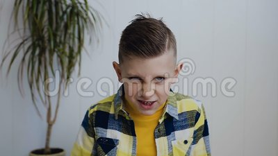 Un muchacho hermoso enojado que se sienta en el piso, mirando en la cámara y mostrando un puño en la cámara indoor El blanco almacen de video
