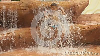 Un niñito está bajo una cascada en el parque acuático almacen de metraje de vídeo