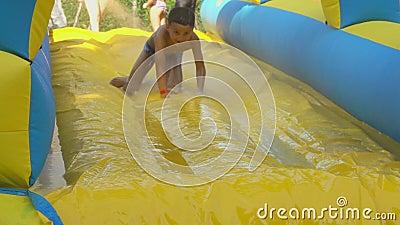 Un niño monta en un tobogán amarillo de espuma en un parque acuático almacen de metraje de vídeo