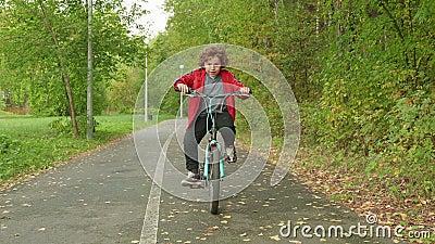 Un niño pequeño montando en bicicleta en el parque de verano. Niño retrato en bicicleta en camino de asfalto en parque de otoñ almacen de video
