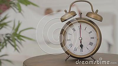 Un orologio antiquato alle 18 con due bionde donne caucasiche che vanno a letto dietro di esso Ragazze stock footage
