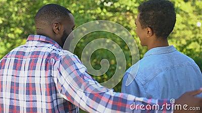 Un père afro-américain embrassant son fils dehors souriant l'un l'autre, connexion familiale banque de vidéos