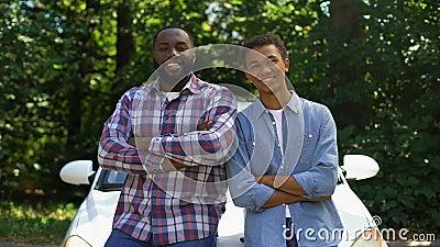 Un père et un fils afrique souriant regardant la caméra sur fond de voiture, aventure de voyage clips vidéos