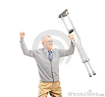 Un paciente feliz del caballero que celebra las muletas y gesticular