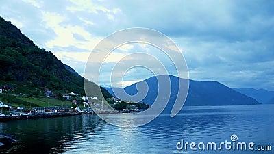 Un paesino pittoresco con case di legno tradizionali alla base di una montagna lungo la costa di Sognefjord in Norvegia stock footage