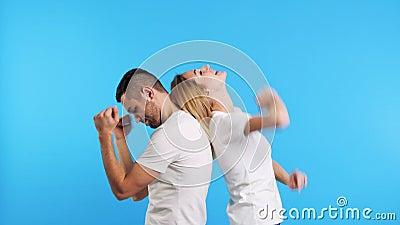 Un paio di ragazze felici ballano insieme in blu su sfondo in studio stock footage