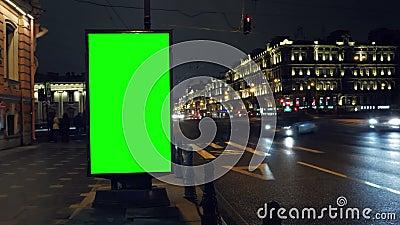 Un panneau d'affichage avec un écran vert sur une rue occupée de nuit clips vidéos