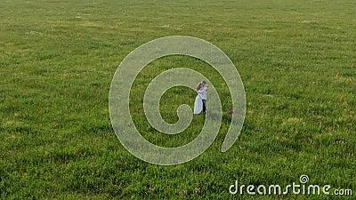 Un par de amantes se alza en medio de un campo de hierba verde Ellos ríen, bailan, besan e inhalan el aroma de almacen de metraje de vídeo