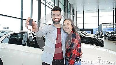 Un par feliz joven compra un nuevo coche Sonríe y muestra las llaves metrajes