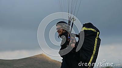 Un parapente masculin élève une aile en plein air sur fond de nuages nocturnes mais ne peut pas voler. panne clips vidéos