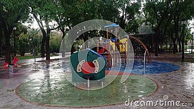 Un parco giochi bagnato vuoto sotto la pioggia archivi video