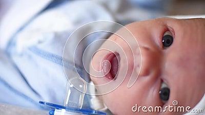 Un pequeño bebé lindo está pareciendo en la cámara y es feliz en una hoja de cama blanca El bebé alrededor y después mira las son almacen de metraje de vídeo