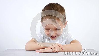 Un pequeño muchacho travieso se sienta en la tabla y las risas, mirando en la cámara Retrato de un muchacho sinceramente de risa  almacen de video