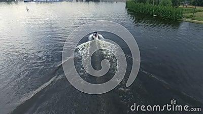 Un petit canot automobile glisse très rapidement au-dessus de la surface de la rivière De l'eau d'ondulation la trace du bateau L banque de vidéos