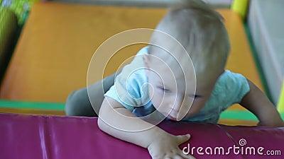 Un petit garçon grimpe au mur avec des obstacles dans le centre de divertissement pour enfants Mouvement lent banque de vidéos