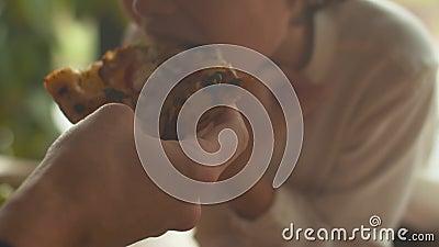 Un petit garçon mange de la pizza au déjeuner dans un café clips vidéos