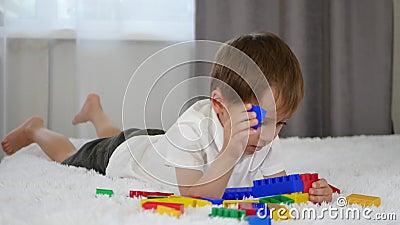 Un petit garçon mignon se trouve sur le lit et joue avec les blocs colorés Constructions d'enfant de meccano banque de vidéos