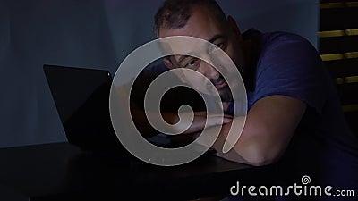Un pirata informático del hombre en un cuarto oscuro se cayó dormido cerca del ordenador trabajos con el código de programa conce almacen de metraje de vídeo