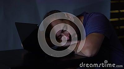 Un pirata informático del hombre en un cuarto oscuro se cayó dormido cerca del ordenador trabajos con el código de programa conce almacen de video
