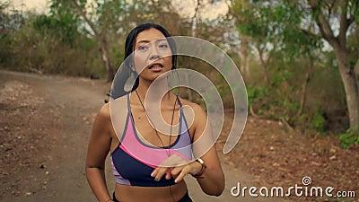 Un pistolet à mouvement lent sur une jeune femme de coureur indonésienne exotique et attirante d'Asie en train de faire du joggin banque de vidéos